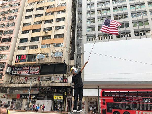 7月1日,銅鑼灣有人舉美國國旗。(張曉慧/大紀元)