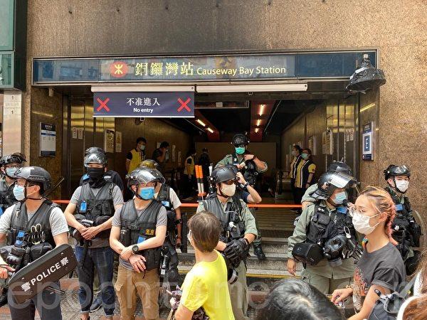 7月1日,港鐵銅鑼灣站E出口被封閉,警員在封鎖線前禁止市民靠近。(文瀚林/大紀元)