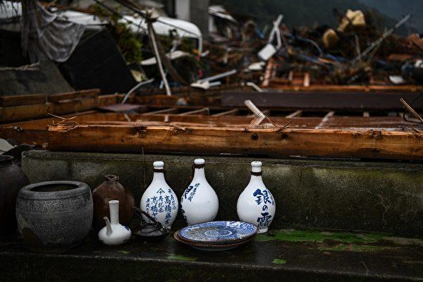 2020年7月10日,強暴雨之後,在熊本縣的球磨村,從受損的房屋中清理出的個人家用物品,如酒瓶子等。(CHARLY TRIBALLEAU/AFP via Getty Images)