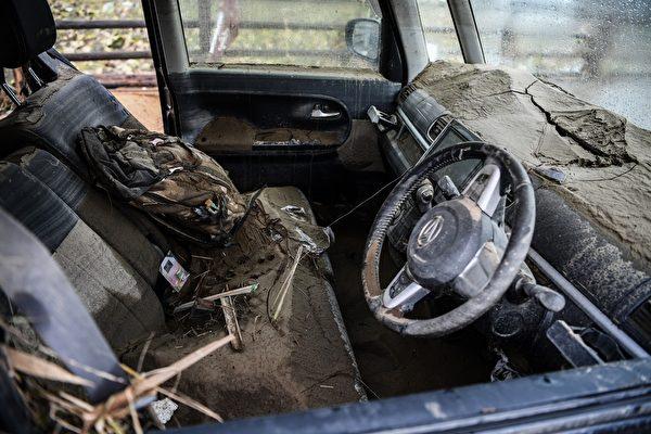 2020年7月10日,在熊本縣人吉市,一輛被暴雨衝入泥土已毀壞的汽車。(CHARLY TRIBALLEAU/AFP via Getty Images)