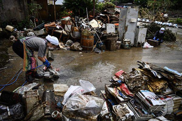 2020年7月10日,熊本縣人吉市,一位居民站在水中清理個人物品。(CHARLY TRIBALLEAU/AFP via Getty Images)
