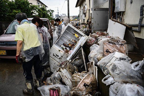 2020年7月10日,在強暴雨之後,熊本縣人吉市的居民清理房屋及被毀壞的個人物品。(CHARLY TRIBALLEAU/AFP via Getty Images)