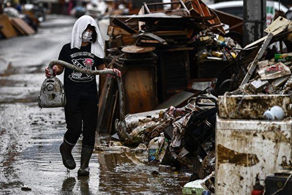 2020年7月10日,在熊本縣人吉市,暴雨後居民進行清理,一名婦女拿著沾滿泥土的吸塵器。(CHARLY TRIBALLEAU/AFP via Getty Images)