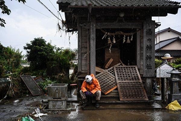 2020年7月10日,在熊本縣人吉市,一位幫助清理的志願者因疲勞在被洪水沖毀的房前休息。(CHARLY TRIBALLEAU/AFP via Getty Images)