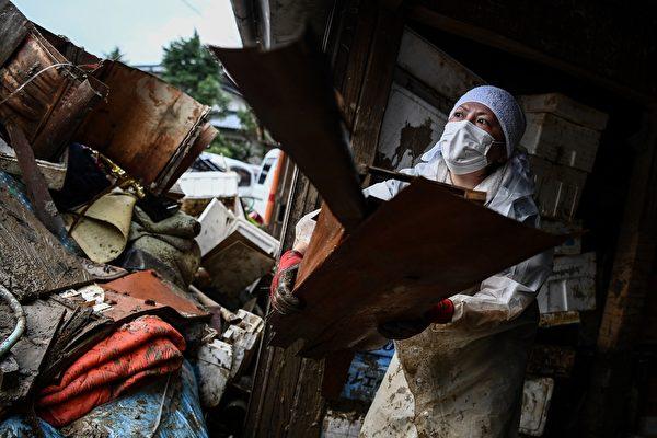2020年7月10日,在強暴雨之後,熊本縣人吉市開始了清理工作,居民在清除房屋內被毀壞的雜物。(CHARLY TRIBALLEAU/AFP via Getty Images)