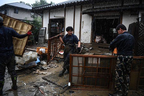 2020年7月10日,在強暴雨之後,熊本縣人吉市開始了清理工作,居民從家中搬出被毀壞的物品。(CHARLY TRIBALLEAU/AFP via Getty Images)