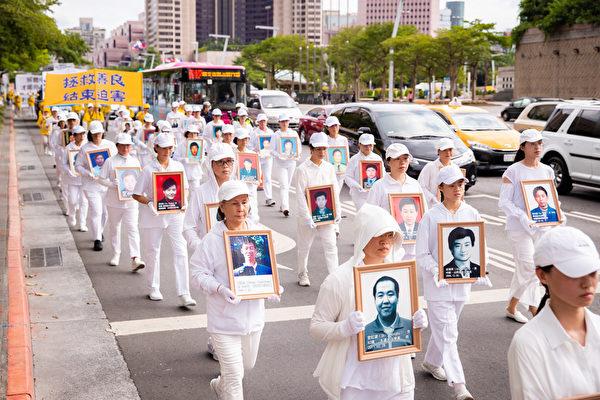 法輪功反迫害21周年,7月18日下午4時,台灣部份法輪功學員約1千人在台北市區舉行「天滅中共 結束迫害」遊行。圖為台灣法輪功學員手持被迫害致死的大陸法輪功學員生前照片。(陳柏州/大紀元)