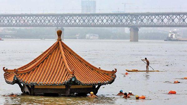 圖為7月8日的武漢,長江水已幾乎淹沒河岸的小亭。(Getty Images)