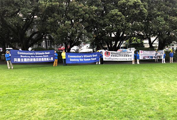 法轮功学员在国会前的草坪打出横幅。(章丰/大纪元)