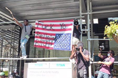 图为7月15日挺警集会中,BLM支持者倒举着写有脏话的美国国旗。