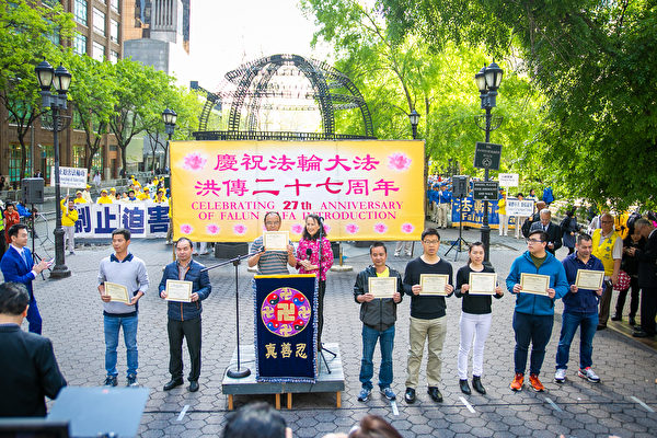 2019年5月16日上午法輪功學員紐約萬人集會,解體中共迫害,支持退黨自救,全球退黨服務中心主席易蓉為八名來自中國大陸的華人在集會上公開「三退」並頒發三退證書。(李莎/大紀元)