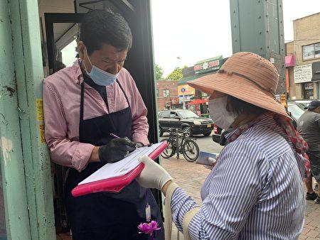 韓裔商家在「解體中共惡魔」倡議書上簽字。(林丹/大紀元)