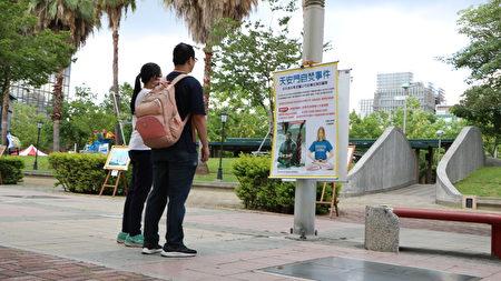 集體煉功場的周圍並置放著法輪功正法21年的圖片,有不少路過的行人駐足觀看。