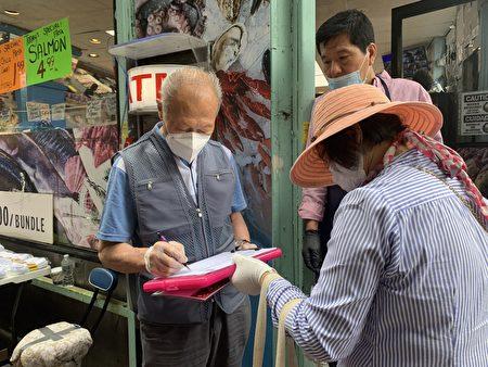 韓裔父子在「解體中共惡魔」倡議書上簽字。(林丹/大紀元)