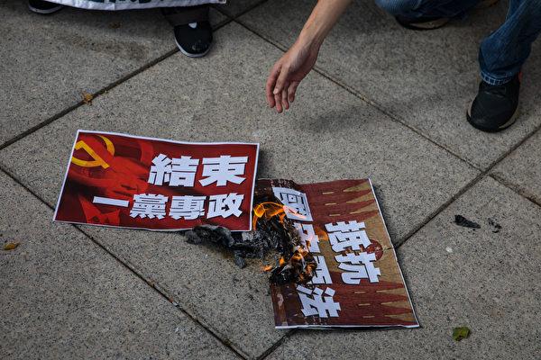 7月1日早上,社民連遊行前往七一升旗禮會場,抗議港版國安法。在現場,遊行成員把寫有訴求的信封及「抵抗國安法」「結束一黨專政」標語燒掉。(DALE DE LA REY/AFP via Getty Images)