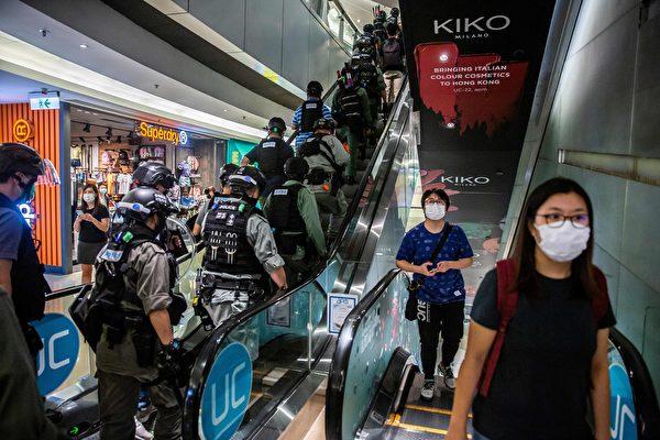 2020年7月6日,香港,購物中心一群防暴警察搭乘向上的電扶梯。(ISAAC LAWRENCE/AFP via Getty Images)