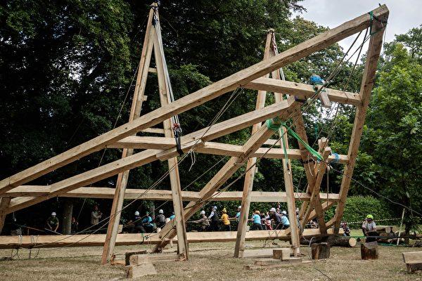 2020年7月7日,法國諾曼第埃曼努維爾(Ermenouville),「無國界木匠」(Charpentiers sans Frontiers)的成員使用繩索舉起了框架,希望可以重建巴黎聖母院大教堂屋頂的桁架。(SAMEER AL-DOUMY/AFP via Getty Images)