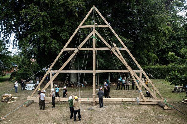 2020年7月7日,法國諾曼第埃曼努維爾(Ermenouville),「無國界木匠」(Charpentiers sans Frontiers)的成員使用繩索舉起了框架。(SAMEER AL-DOUMY/AFP via Getty Images)