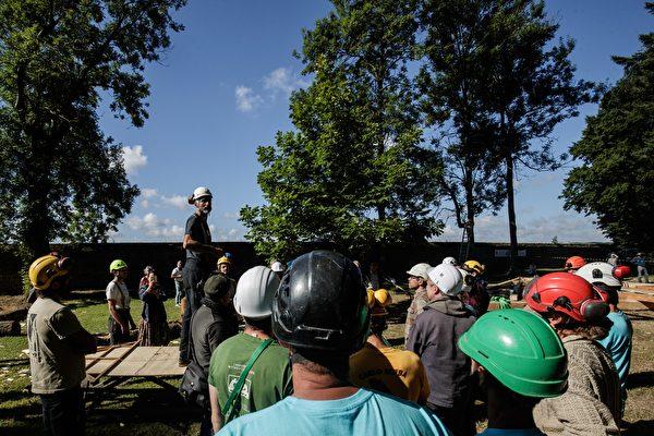 2020年7月7日,法國諾曼第埃曼努維爾(Ermenouville),在眾人抬起框架之前,首席木匠進行指導。(SAMEER AL-DOUMY/AFP via Getty Images)