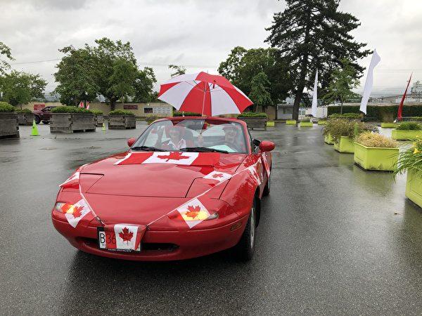 圖:PNE舉辦加拿大國慶日汽車遊行,雨中體驗別樣的節日喜慶。圖為Karoline夫婦。(邱晨/大紀元)