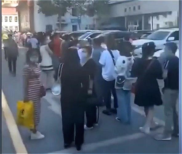 7月18日,新疆烏魯木齊宣佈全市進入疫情防控「戰時狀態」。圖為7月16日,烏魯木齊人民醫院前,人們排長隊檢測核酸。(影片截圖)