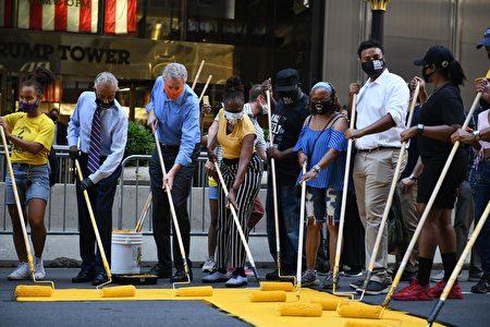 左二起:非裔民權領袖、紐約市長白思豪和市長夫人麥克蕾在川普大廈門前,塗上「Black Lives Matter」標語。