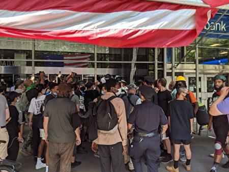 支持BLM的民眾與警方發生近距離衝突,聚集在百老匯250號的市議會辦公樓一樓門口前。
