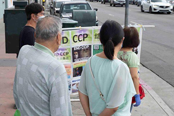 唐人街的顧客在觀看真相圖片展。(周容/大紀元)