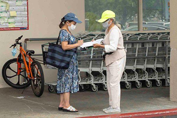 華人超市的顧客在拒絕中共的徵簽薄上簽字。(周容/大紀元)