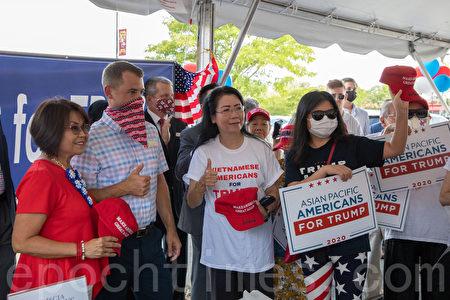 特朗普競選團隊高級顧問約翰・彭斯(John Pence)將帶有特朗普親筆簽名的帽子贈送給亞裔社區助選志願者。(林樂予/大紀元)