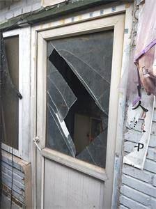北京法輪功學員周晶家大門玻璃被砸碎。(明慧網)