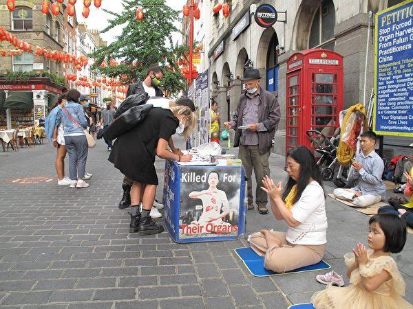 三位意大利青年在倫敦唐人街簽名支持法輪功反迫害。(明慧網)