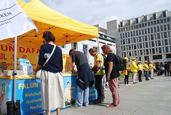 法輪功學員在柏林勃蘭登堡門前的廣場上舉辦信息日活動,傳播法輪功真相。(明慧網)