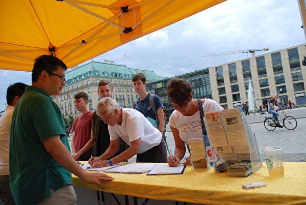 安尼亞(Anja)和先生在簽字,希望為法輪功爭取尊嚴和自由。(明慧網)