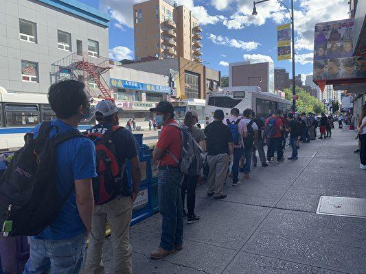 地鐵7號線雙線停擺,大批乘客在法拉盛地鐵口排隊等待接駁巴士,先坐接駁巴士到74街,然後再轉地鐵到曼哈頓。(林丹/大紀元)