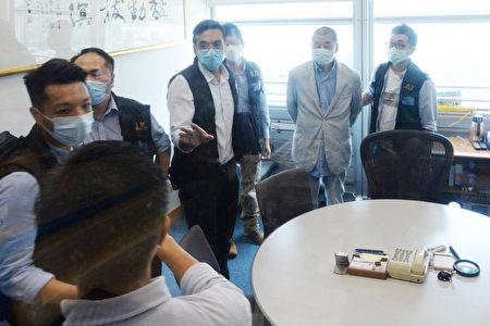 香港《蘋果日報》創辦人黎智英(右2)被扣上手銬,押送到《蘋果日報》大樓內協助查證。(中央社)