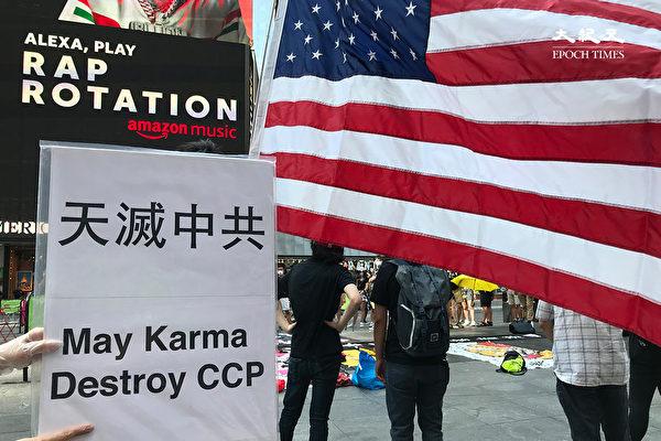 參與「NY4HK」活動的民眾,手持寫有「天滅中共」的展版。(林宜君/大紀元)