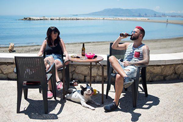 武漢肺炎(新冠肺炎、Covid-19)疫情又開始回溫,且新增病例有年輕化的趨勢。圖為西班牙全國封鎖下,人們來到馬拉加海邊的露台酒吧。(JORGE GUERRERO / AFP)