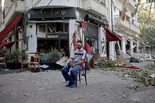 2020年8月5日,黎巴嫩Mar Mikhael街區,爆炸後一名受傷的男子坐在街上。(PATRICK BAZ/AFP via Getty Images)