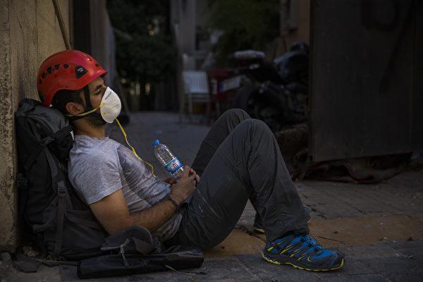 2020年8月5日,黎巴嫩貝魯特,爆炸後一名男子靠著牆休息。(Daniel Carde/Getty Images)