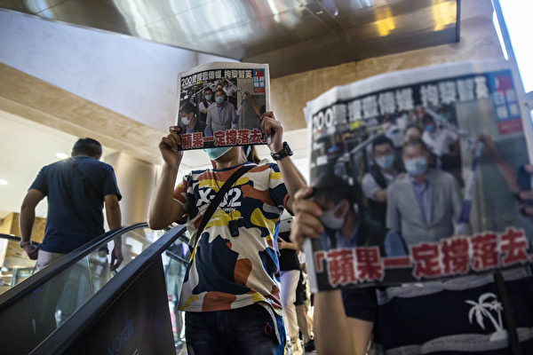 8月11日,港人在商場中,舉著《蘋果日報》表示抗議。(ISAAC LAWRENCE/AFP via Getty Images)