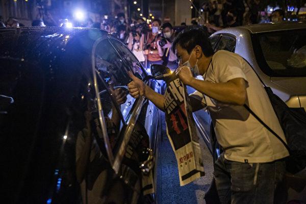 8月12日凌晨,港人在旺角警署举着《苹果日报》表示抗议,图为港人向刚获释、已坐在车中的黎智英竖起大拇指,表示支持。(ISAAC LAWRENCE/AFP via Getty Images)