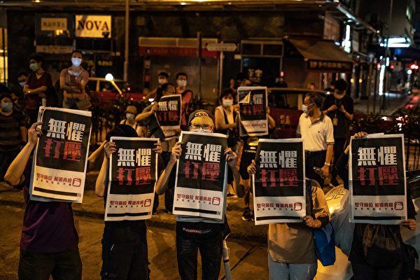 8月12日凌晨,港人在旺角警署等候黎智英获释,高举《苹果日报》以示抗议。(Anthony Kwan/Getty Images)