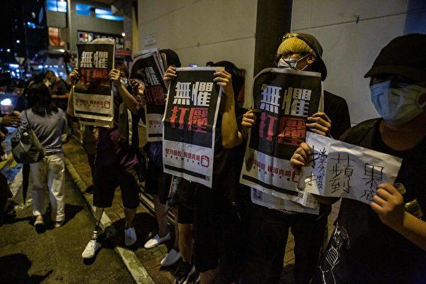 8月12日凌晨,港人在旺角警署等候黎智英获释,高举《苹果日报》以示抗议。(ISAAC LAWRENCE/AFP via Getty Images)