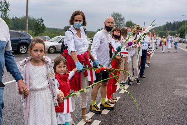 2020年8月23日,立陶宛的幾萬民眾手持鮮花,揮舞著白俄反對派的紅白旗幟和立陶宛國旗,手牽手從立陶宛首都維爾紐斯延伸到白俄羅斯邊界,形成一條綿延35公里的人鏈。(Arturas Morozovas/Getty Images)