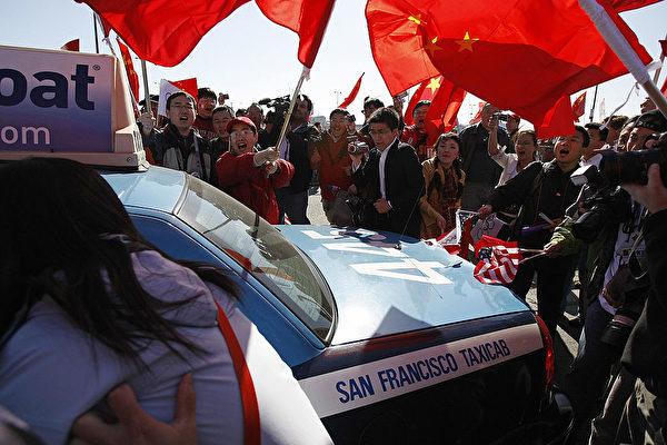 2008年4月9日,奧運火炬傳遞到達美國三藩市,中領館調集數千名學生,與當地抗議人群對峙。圖為親共者包圍了一輛西藏抗議者乘坐的的士。(ROBYN BECK/AFP via Getty Images)