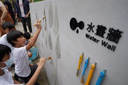 孩子们在户外水画墙上画出水滴状图案。