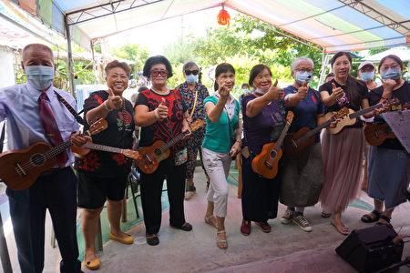 一群快乐的长者唱着歌、弹着乌克丽丽,欢迎县长张丽善莅临揭牌。