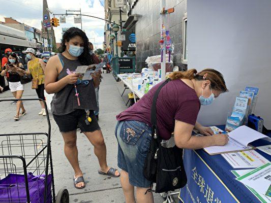 民眾在法拉盛緬街,在EndCCP倡議書的徵簽表上簽名。(林丹/大紀元)