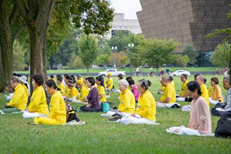 9月27日上午,華盛頓DC的部份法輪功學員在白宮對面的華盛頓紀念碑下煉功,向路人講述法輪功真相。(林樂予/大紀元)